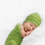 One week old baby boy posed sleeping on a white IKEA blanket in photographer's studio for his newborn portraits. Wears a lime green ruffled newborn cocoon. Shot by Hilary Beaumont of Lunaria Photography based in Whitby, Ontario.One week old baby boy posed sleeping on a white IKEA blanket in photographer's studio for his newborn portraits. Wears a lime green ruffled newborn cocoon. Shot by Hilary Beaumont of Lunaria Photography based in Whitby, Ontario.