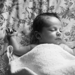 Two week old baby boy laying on bedspread for lifestyle newborn photography shoot. Shot by Hilary Beaumont of Lunaria Photography in Wellington, Ontario.