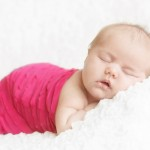 Two week old baby girl posed sleeping on a white IKEA blanket in photographer's studio for her newborn portraits. Wears a hot pink ruffled newborn cocoon. Shot by Hilary Beaumont of Lunaria Photography.