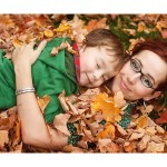 Mother son portrait laying in fall leaves. Taken by Hilary Beaumont of Lunaria Photography based in Whitby, Ontario.