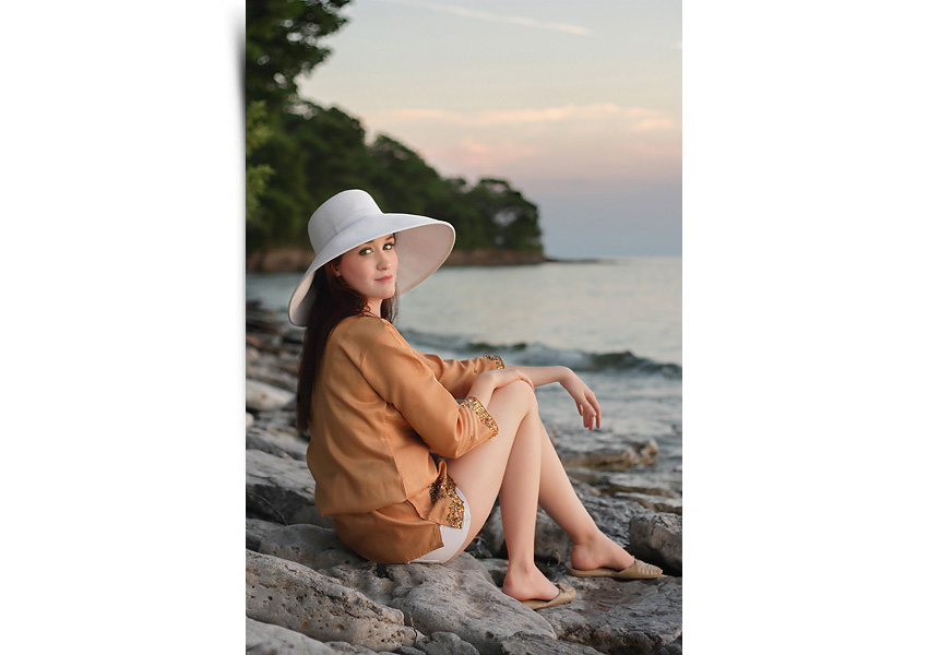 Senior girl portrait sitting on beach at sunset. Shot by Hilary Beaumont of Lunaria Photography.