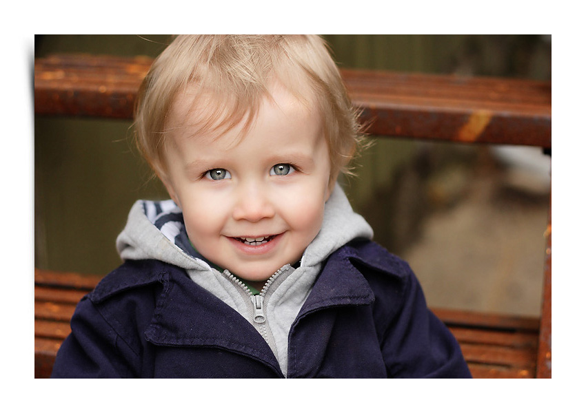 Two year old boy portrait on steps in alleyway of Markham, Ontario captured by Hilary Beaumont of Lunaria Photography.