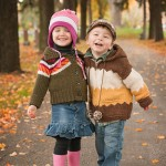 Two three year olds- girl and boy- laugh as they have their portrait taken amidst fall foliage by Hilary Beaumont of Lunaria Photography.