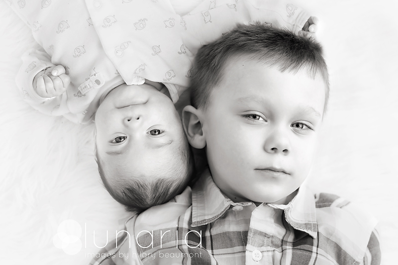 Sibling shot of newborn girl and young boy shot by Hilary Beaumont of Lunaria Photography.